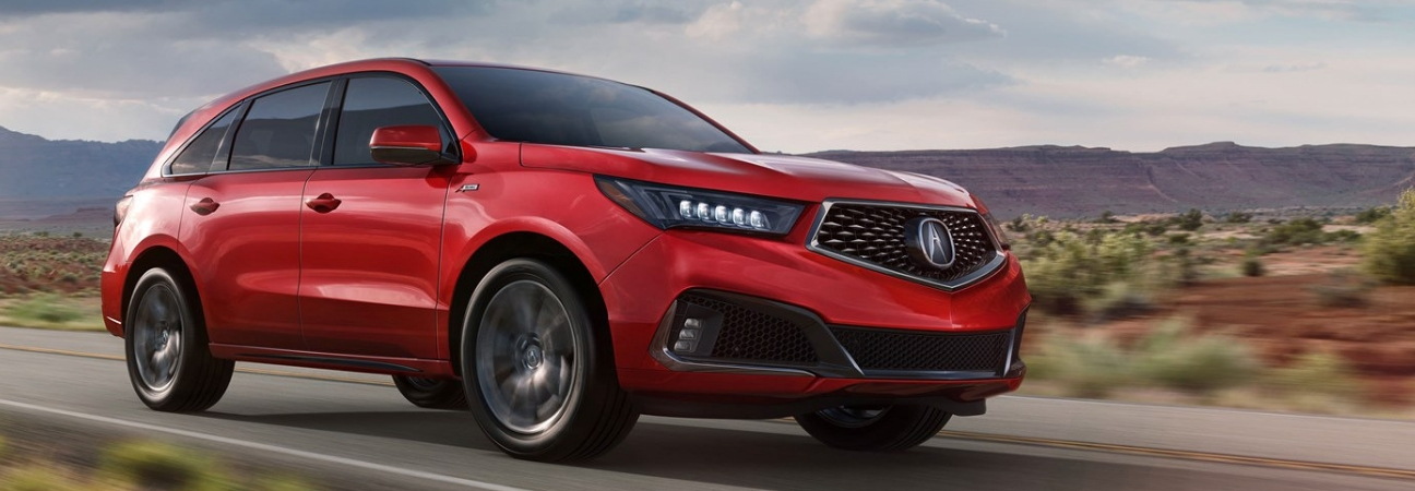 A Red 2019 Acura Mdx Driving Down The Road